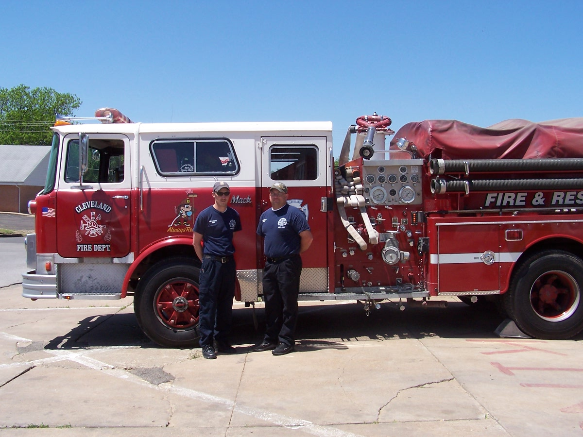 Two men standing next to a large fire truck