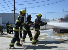 Three firefighters holding and spraying a fire hose