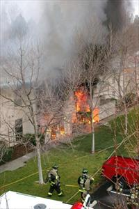 Firefighters approaching a house that is engulfed in flames