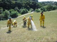 A group of firefighters pulling a fire hose up a large hill
